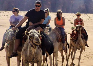 Joshua Brown and other students riding camels