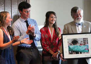2015 graduates; Kenna Rewcastle, Rebecca DiGiovanna, and R.J. Vogt, present Professor Kovac with a class gift at the end of the award ceremony.